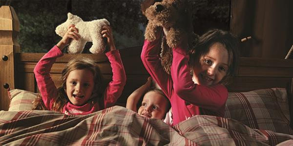 Children, cosy in the bed with soft toys