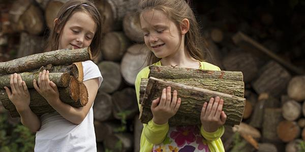 Young children carrying chopped wood
