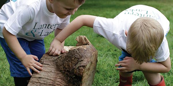 Children discovering nature looking under a log
