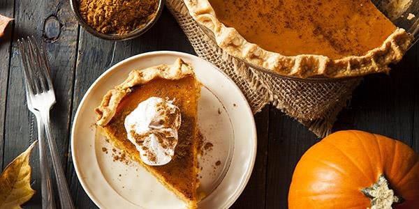 Pumpkin pie next to pumpkin on table