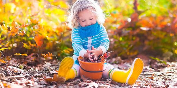Toddler enjoying autumn leaves