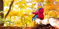 Child enjoying autumn leaves