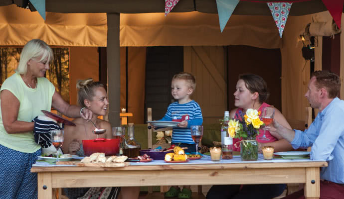 Family enjoying a meal whilst on their glamping holiday