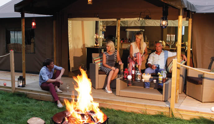 A family group realxing by thw fire pit of their glamping tent