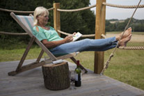 Woman enjoying the sunshine in a chair on the porch outside the tent - thumbnail