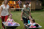 Kids having fun rides in the wheel barrow