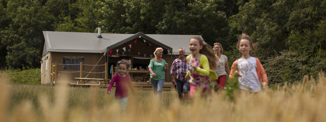 Family goes out of the glamping tent into the fields