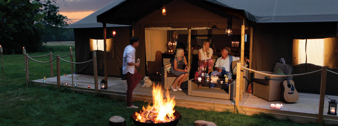 Family enjoying evening drinks on the terrace by the fire in Sweffling Farm glamping site